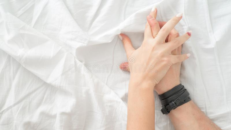 肉欲的美好的年轻夫妇有在床上的性 拉扯在销魂,性交高潮的女性手白色板料 概念亲吻妇女的爱人 免版税库存图片