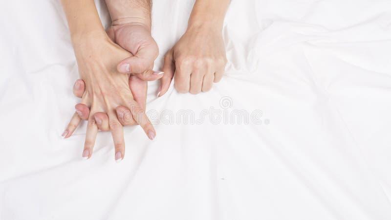 肉欲的美好的年轻夫妇有在床上的性 拉扯在销魂,性交高潮的女性手白色板料 概念亲吻妇女的爱人 免版税库存照片