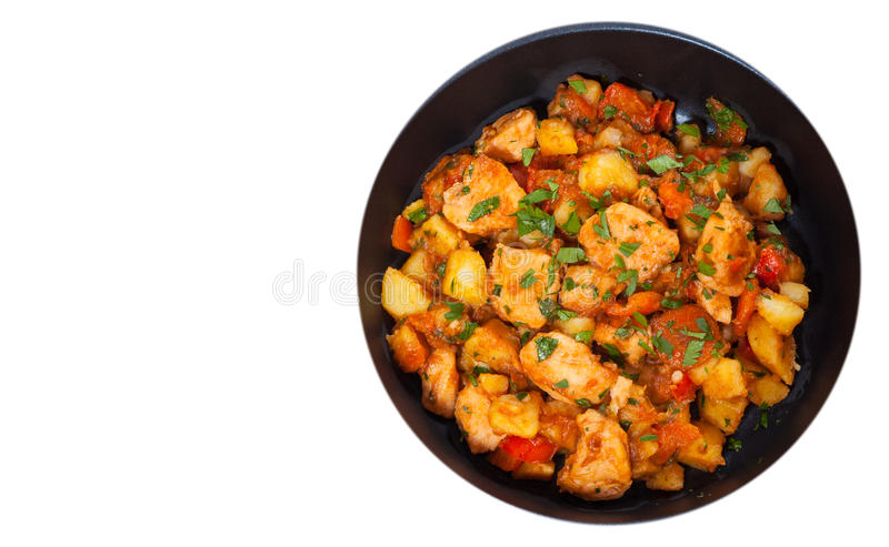肉炖煮的食物用土豆、胡椒、葱和红萝卜在煎锅 顶视图 查出 库存图片