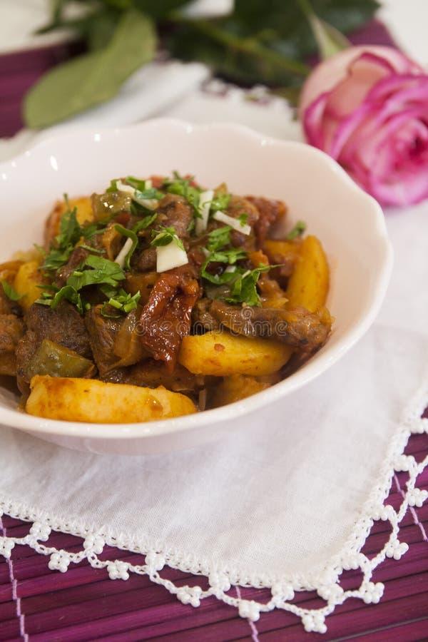 肉炖煮的食物用土豆和香料、蕃茄、黄瓜和绿色 墩牛肉 库存图片