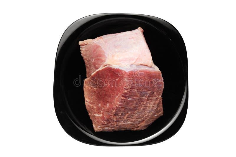 肉片在白色背景的一个黑色的盘子在 免版税图库摄影