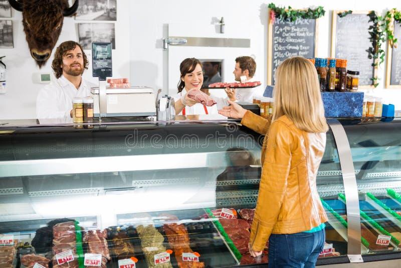 给肉的女推销员女性顾客 免版税库存照片