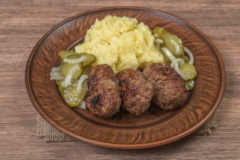 肉自创炸肉排用在陶器的土豆泥 browne 库存图片