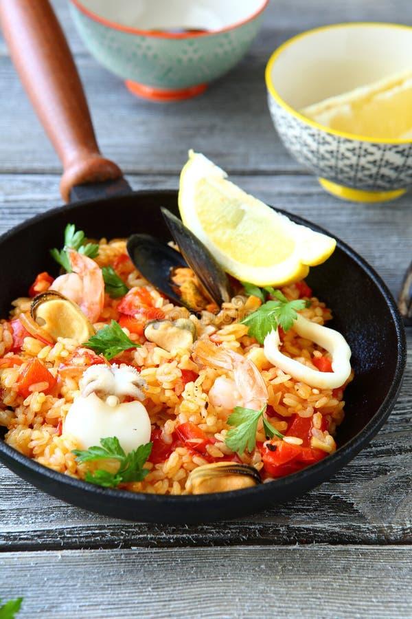 肉菜饭用大虾、淡菜和柠檬在煎锅 免版税库存照片