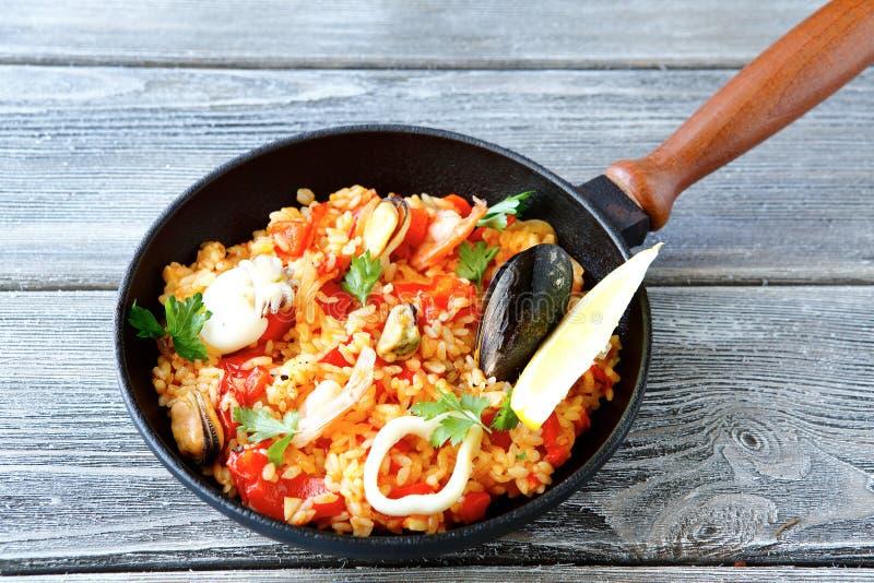 肉菜饭用虾、淡菜、柠檬和米在煎锅 免版税库存照片