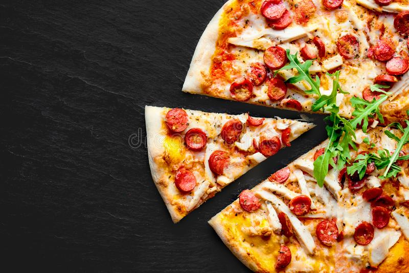 肉薄饼用香肠、无盐干酪乳酪和蕃茄在黑色 免版税库存图片