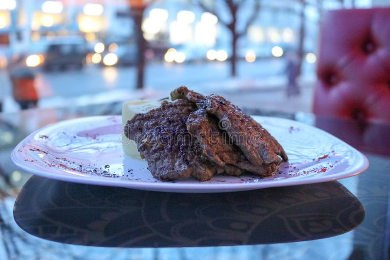 肉,猪肉,在一块白色板材的牛肉在咖啡馆的一张桌上,餐馆在晚上 库存图片