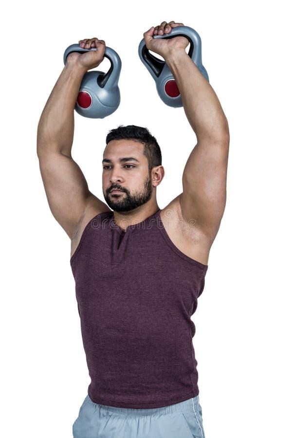 肌肉严肃的人举的kettlebells 免版税库存照片