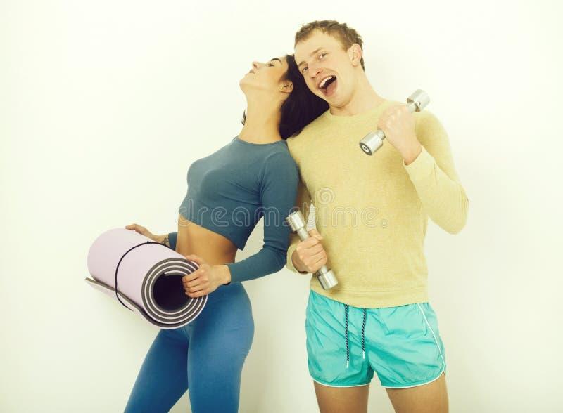 肌肉人和女孩健身房的与哑铃和席子 图库摄影