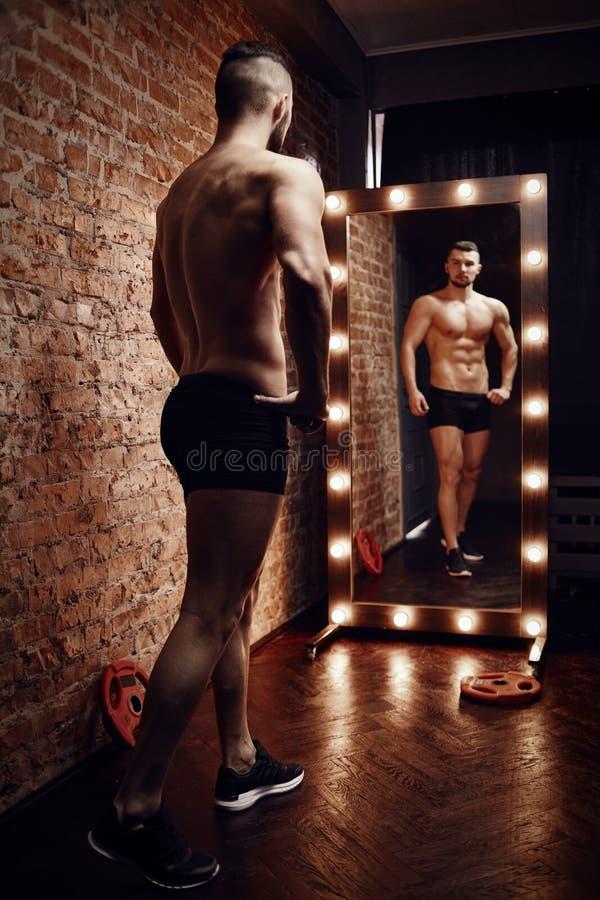 年轻肌肉人和镜子 免版税库存图片