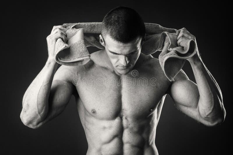肌肉人喝在黑暗的背景的水 免版税库存照片