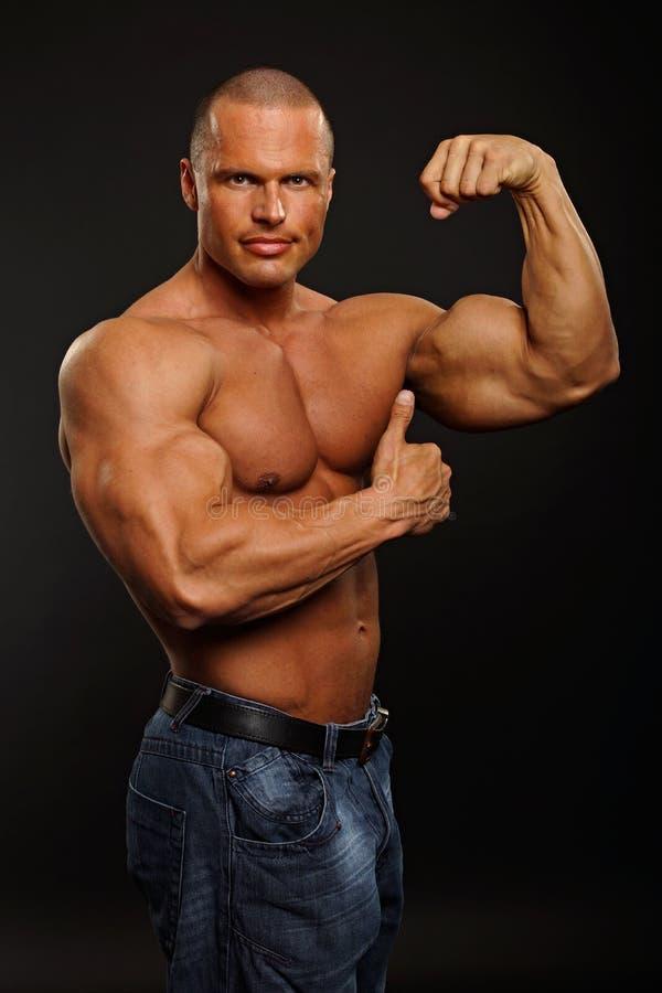 肌肉人展示胳膊 免版税库存照片