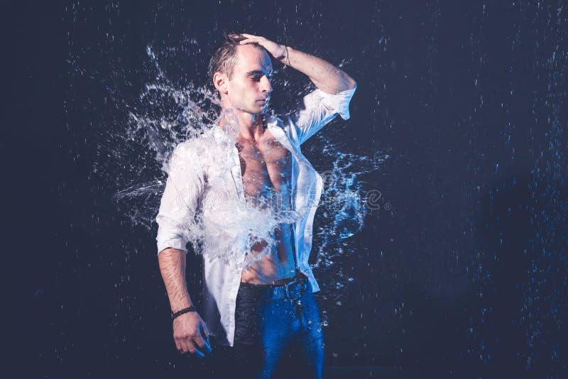 肌肉人新鲜的画象用水在黑暗的背景飞溅 免版税库存图片