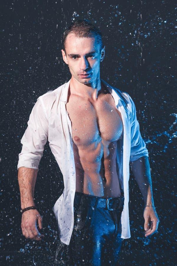 肌肉人新鲜的画象用水在黑暗的背景飞溅 图库摄影