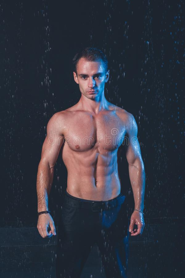 肌肉人新鲜的画象用水在黑暗的背景飞溅 免版税图库摄影