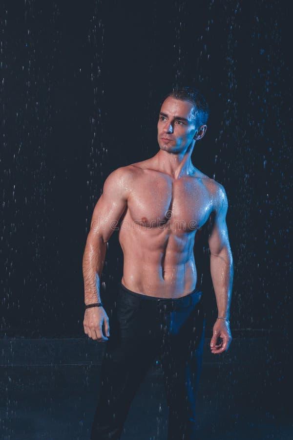 肌肉人新鲜的画象用水在黑暗的背景飞溅 免版税库存照片