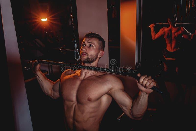 肌肉做在健身房的爱好健美者英俊的人锻炼与赤裸躯干 有腹肌和二头肌的坚强的运动人 免版税库存图片