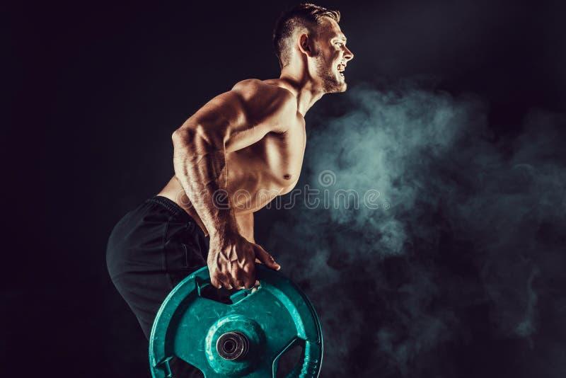 肌肉做锻炼的爱好健美者英俊的人 免版税库存图片