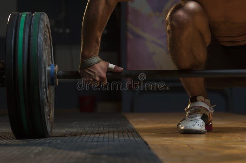 年轻肌肉在健身房,特写镜头的人举的杠铃 免版税库存图片