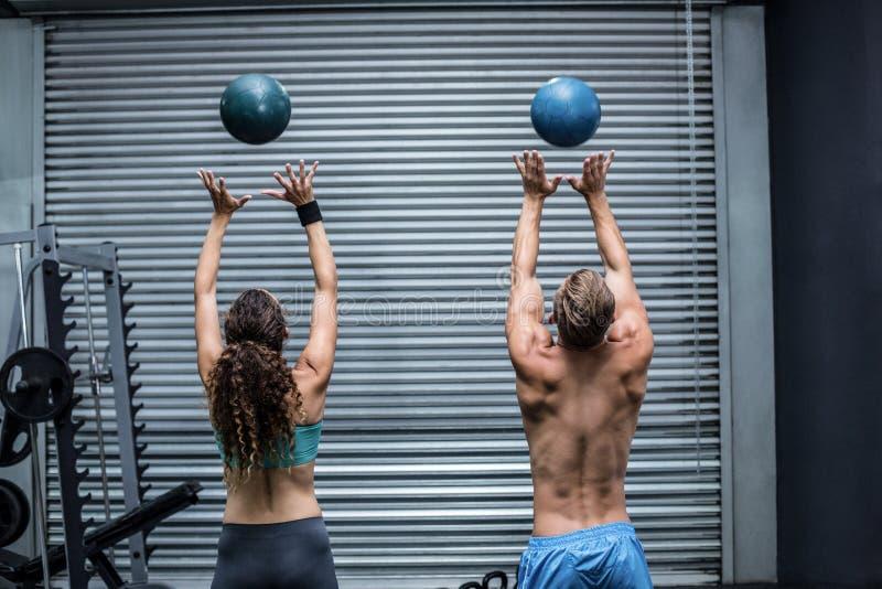 肌肉夫妇投掷的球在天空中 免版税库存图片