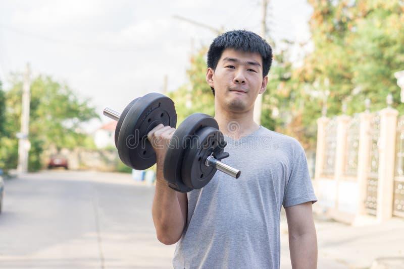 肌肉年轻亚裔人举的重量在公园 健康概念 库存照片