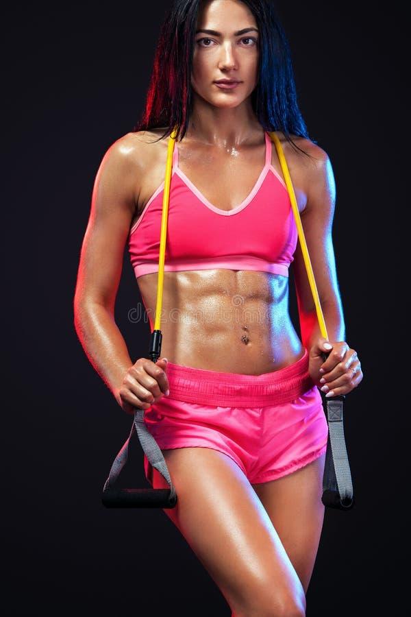 肌肉年轻人适合的体育女子运动员 与带或扩展器的锻炼在黑背景的健身房 强胃肠 库存图片