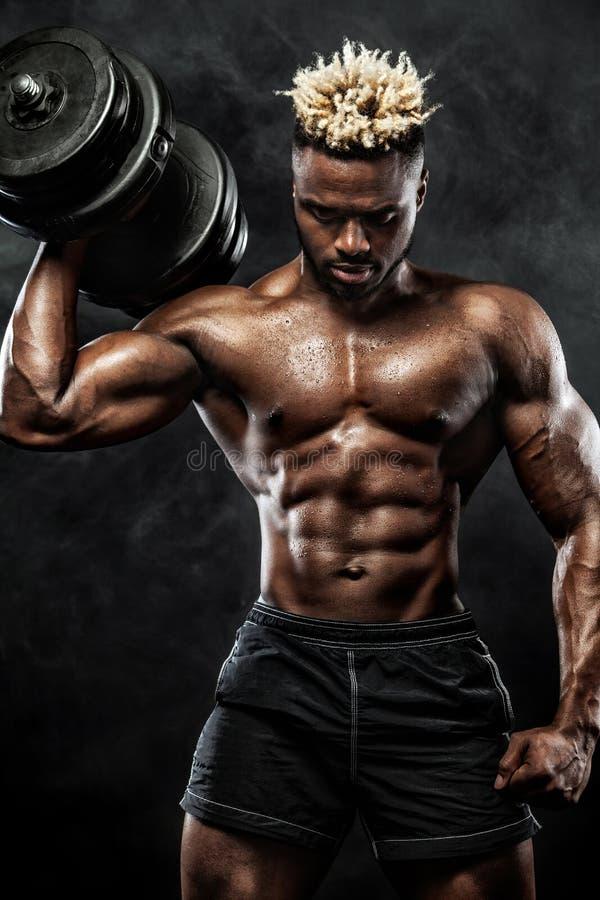 肌肉年轻健身炫耀与哑铃的人锻炼在健身健身房 免版税库存图片