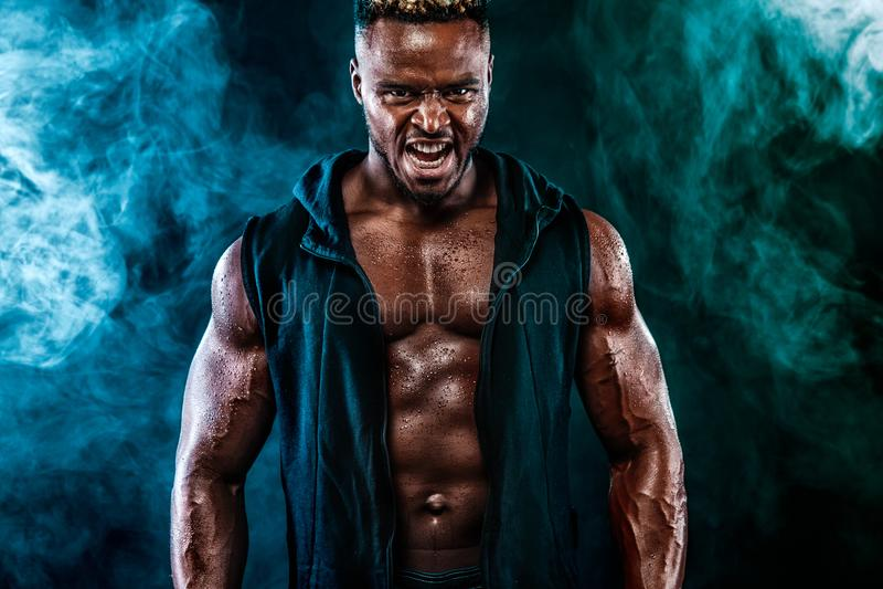 肌肉年轻健身炫耀与哑铃的人锻炼在健身健身房 免版税库存照片