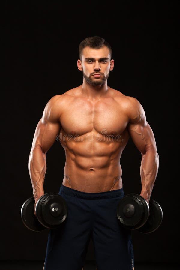 肌肉英俊的人训练与在健身房的哑铃 隔绝在与Copyspace的黑背景 库存图片
