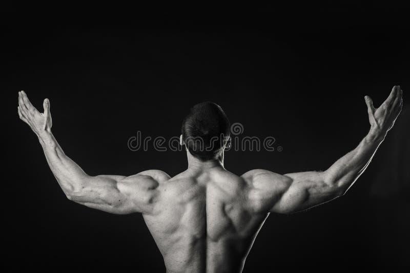 肌肉运动员展示他的肌肉在黑暗的背景的装载下 库存照片
