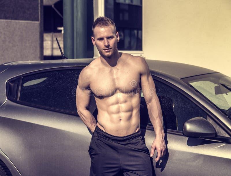 肌肉露胸部的人在汽车外面 免版税图库摄影