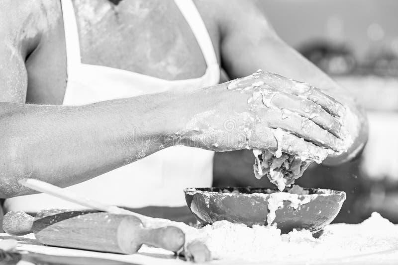 肌肉面包师或厨师揉的面团的手在碗的 厨师的手烹调与面团和面粉一起使用 碗用面团 免版税库存图片
