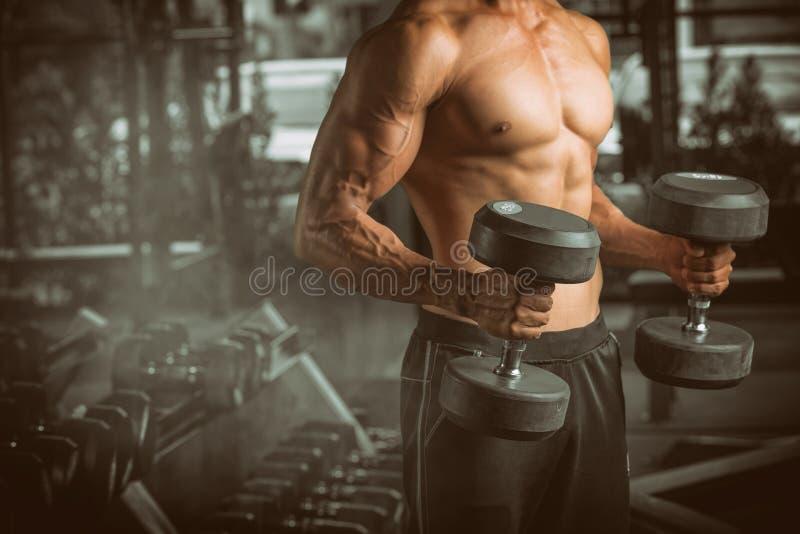 肌肉年轻人举的重量在健身中心 免版税库存照片