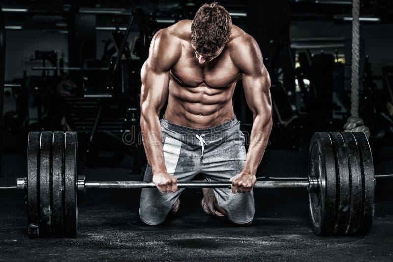 肌肉年轻健身炫耀与杠铃的人锻炼在健身健身房 免版税图库摄影