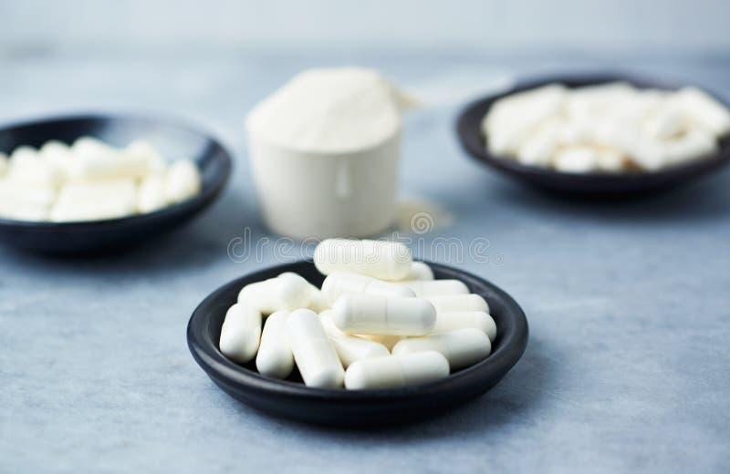 肌酸、Beta胺基代丙酸、牛磺酸胶囊和乳清蛋白瓢  库存图片