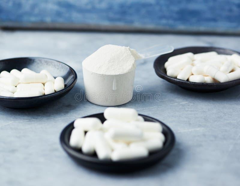 肌酸、Beta胺基代丙酸、牛磺酸胶囊和乳清蛋白瓢  在石头/木背景的建身的食物补充 免版税库存图片