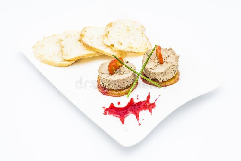 肝泥用蕃茄、绿色、薄脆饼干和调味汁 免版税库存照片