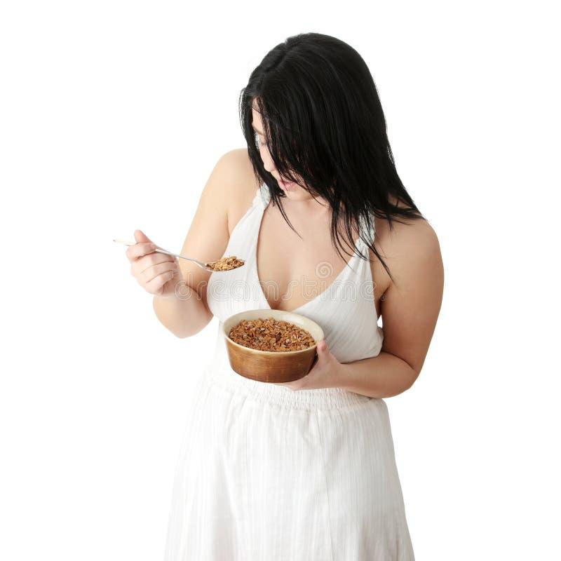肥头大耳的吃平纹细布妇女年轻人 库存图片