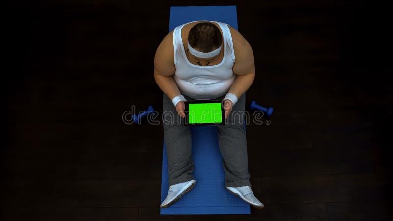 肥头大耳的男性卷动片剂坐的健身房,读健康生活方式文章 免版税库存照片