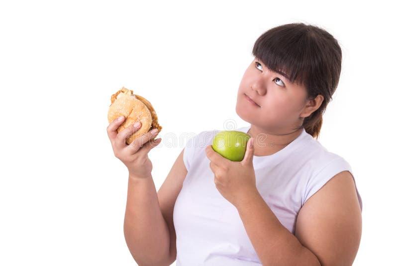 肥胖亚裔妇女佩带的白色T恤杉和选择吃油煎 库存照片