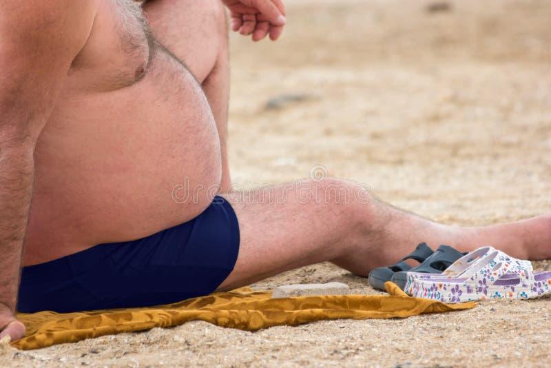 肥胖人坐海滩 免版税库存图片