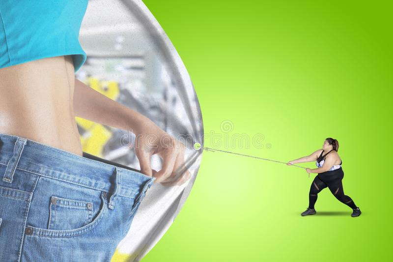 肥胖人拉扯与亭亭玉立的腹部的一副横幅 免版税库存照片