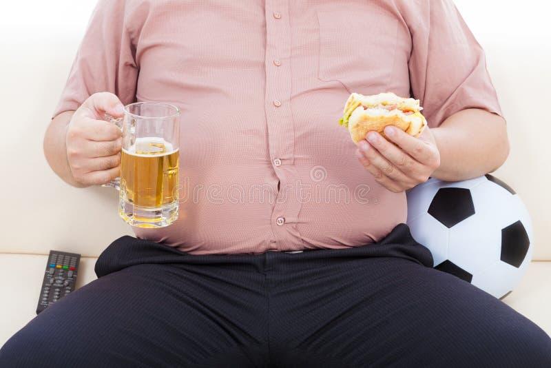 肥胖企业食人食物和啤酒和坐沙发 免版税库存图片