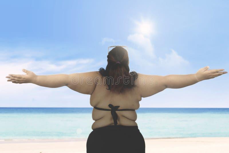肥胖在海滩的妇女佩带的游泳衣 免版税库存图片