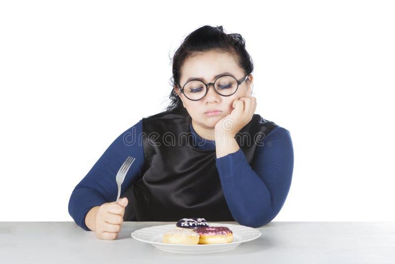 肥胖女性犹豫吃油炸圈饼 免版税库存图片
