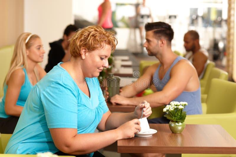 肥胖妇女喝咖啡在健身房 库存照片