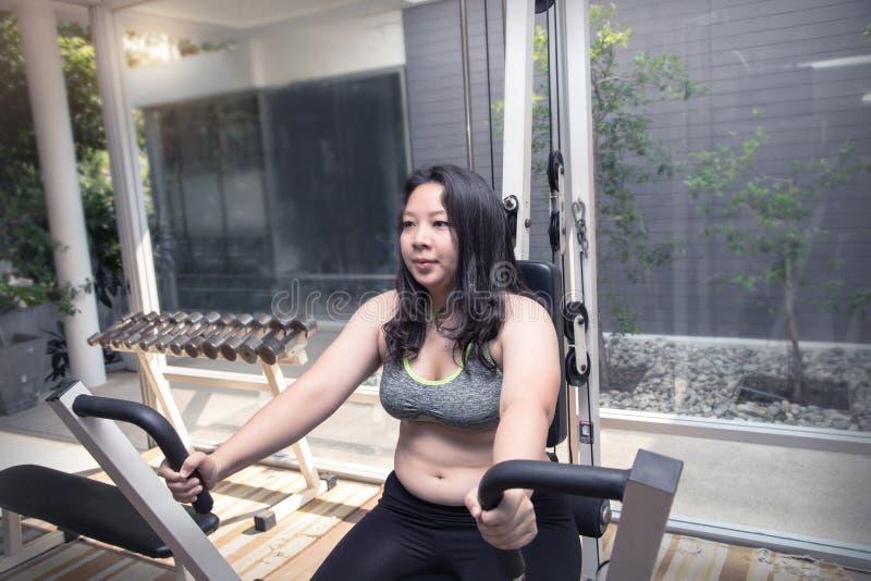 肥胖妇女在推挤胳膊机器的乏味疲倦的面孔锻炼减重放弃锻炼概念 免版税库存图片