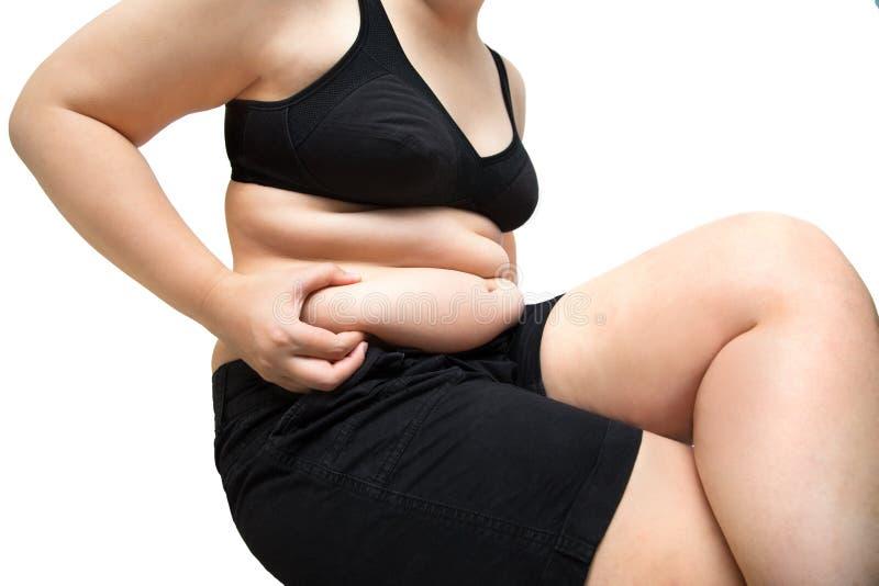 肥胖妇女挤压腹部肥胖佩带的黑内衣胸罩和pa 库存照片