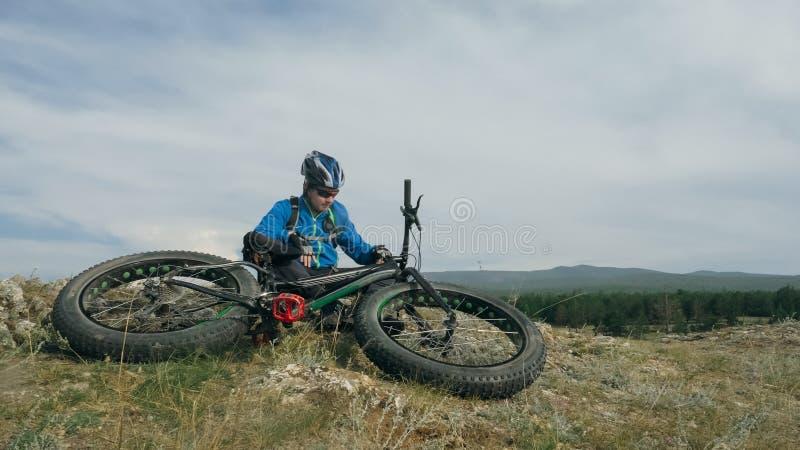 肥胖自行车在驾驶小山的夏天也叫了fatbike或肥胖轮胎自行车 库存图片
