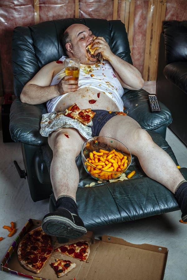肥胖食人和观看的电视 库存图片